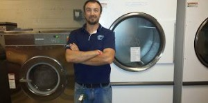 Jon Pell of National Laundry Equipment proudly stands next to the brand new Huebsch OPL laundry system now used by the Tennessee Titans!