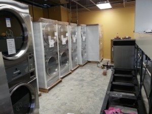 Some coin operated dryers still crated waiting to be installed in a brand new laundry.